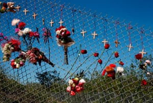 Flowers and crosses line a fence near the school on a makeshift memorial for the victims of the Marjory Stoneman Douglas high school shooting.