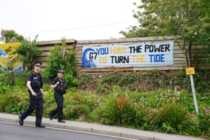 Police officers walk past a banner in Carbis Bay