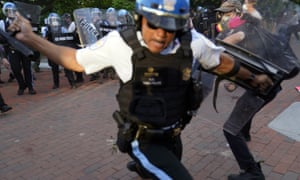 An officer swings a baton as demonstrators clash with police near the White House in Washington on 30 May.