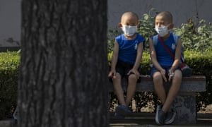 Children wearing masks to curb the spread of the coronavirus sit on a bench in Beijing, China on Monday, July 13, 2020.