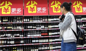 A consumer walks by wine products on the goods shelf at a supermarket in Beijing. China has announced tariff hikes on a list of US goods.