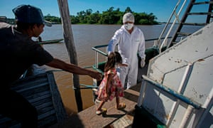 A health worker from the Medical Care Ship Unit UBS attends a girl at the riveside community of Salvacao, on the river Ipiranga, municipality of Melgaco in Marajo Island, state of Para, Brazil, during the coronavirus pandemic.