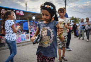 A girl holds toy guns and ice cream in Tandarei