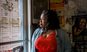 Angie Thomas in a red dress looking out of the window