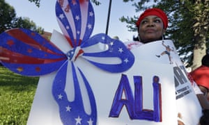 Frances Woods holds a sign saluting Muhammad Ali as she awaits his funeral procession to make its way down Muhammad Ali Boulevard in Louisville, Kentucky.