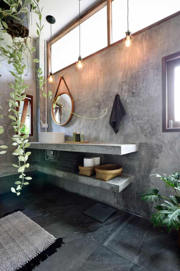 Vanity in a luxurious concrete bathroom with candles, hanging plants and soaps.