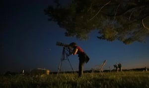 Astronomy enthusiasts watch the lunar eclipse of the moon in the southern Bavarian village of Raisting, near Munich, Germany.