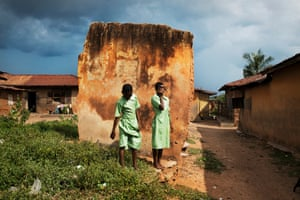 Two young students pose next to their house in the old city of Igbo-Ora.