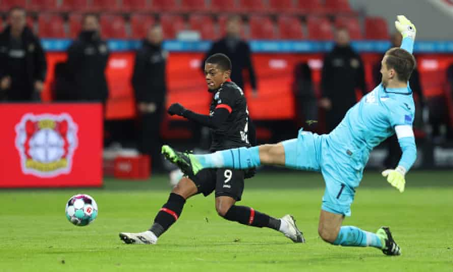 Leon Bailey scores his second goal for Leverkusen against Hoffenheim despite the efforts of Oliver Baumann.