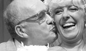 Coronation Street barmaid Bet Lynch (actor Julie Goodyear) gets a kiss from her groom Gilroy in 1987.