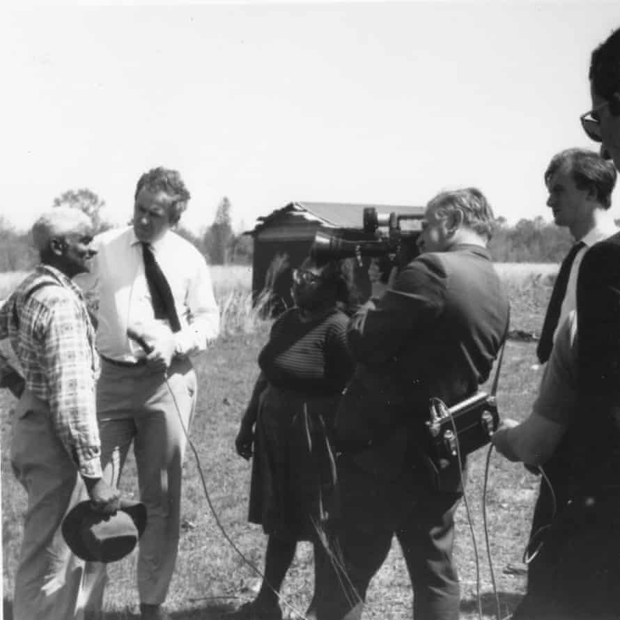 Black and white photo of a man being interviewed by two people, one holding a microphone, the other a camera