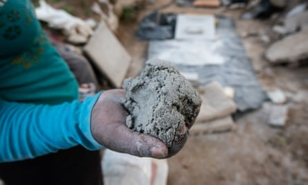 A woman employed as a rock crusher in the abandoned mining town of Durban Deep shows a handful of earth that will be processed to extract gold