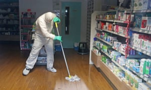 A man in protective clothing cleaning the County Oak Medical Centre GP practice in Brighton.