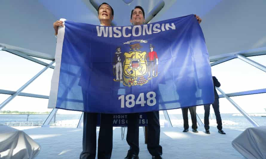 Foxconn chairman Terry Gou, left, and governor Scott Walker hold the Wisconsin flag to celebrate the company's $10bn investment to build a display panel plant in Wisconsin.