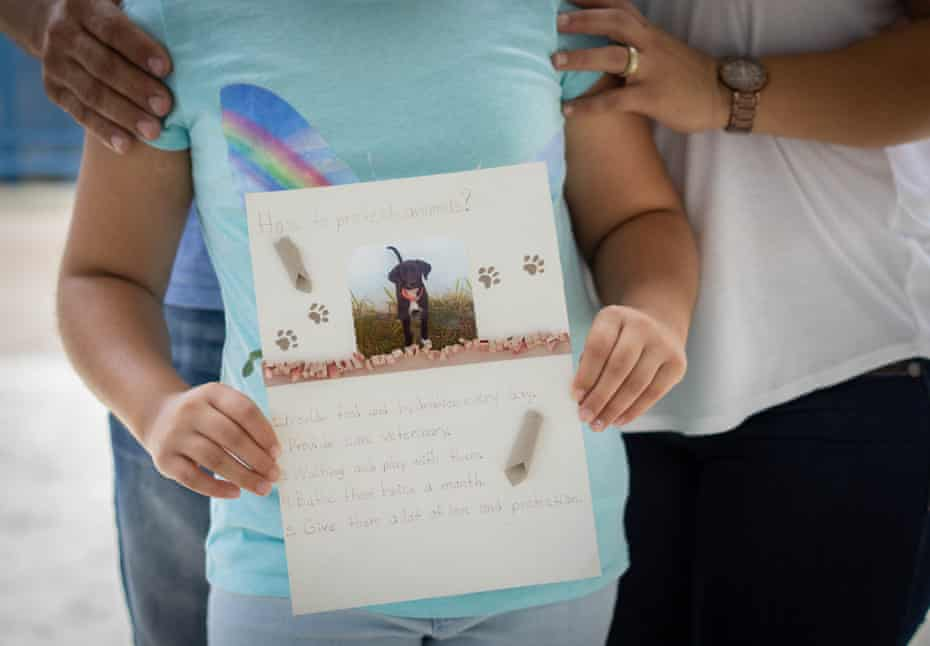 Alejandra, 9, with her parents, holds a photo of her dog Nisan used for a school project.