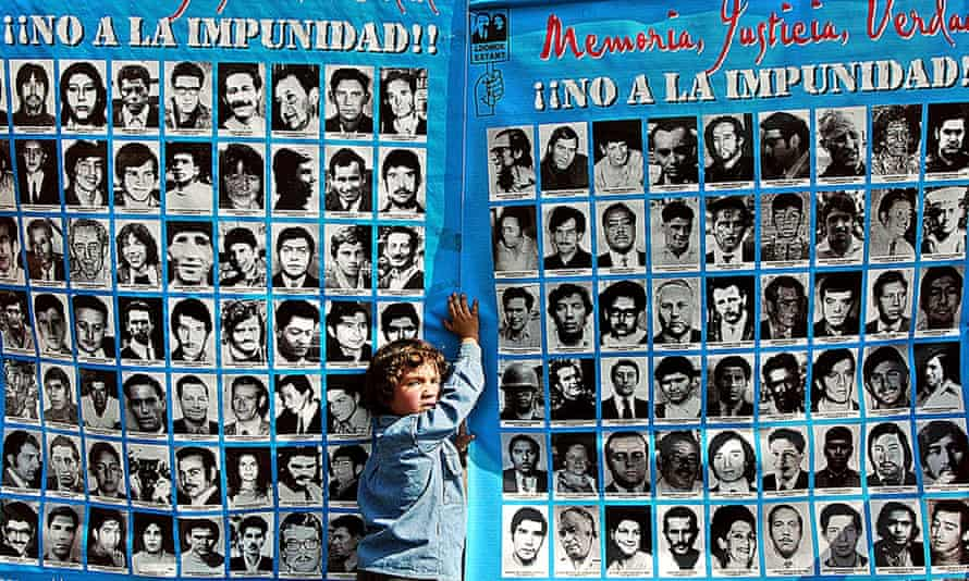 A boy holds a banner with pictures of some of the 3,000 people killed or disappeared during Augusto Pinochet's dictatorship (1973-90). Pinochet faced charges over the deaths of political opponents under Operation Condor.