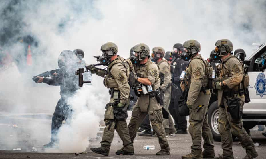 Riot police points weapons as they move through a cloud of teargas at a Black Lives Matter protest in Denver.