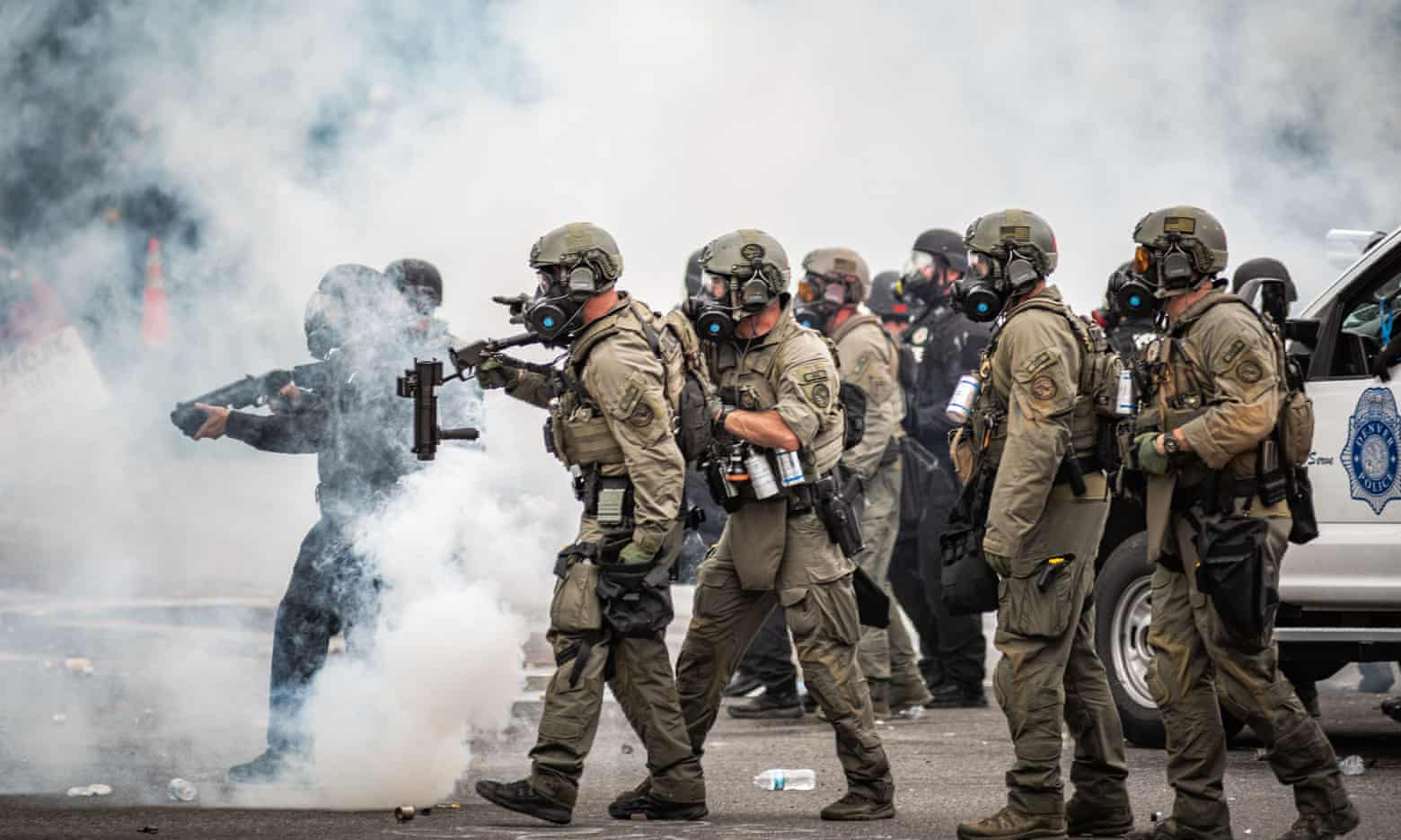 Riot police points weapons as they move through a cloud of teargas at a Black Lives Matter protest in Denver. Photograph: Paul Winner/REX/Shutterstock
