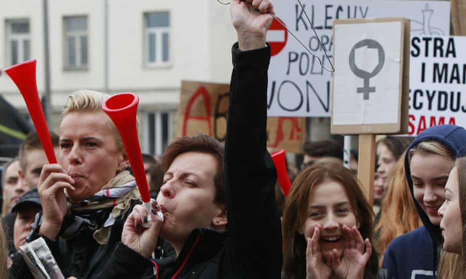 Polish women and some male supporters blow horns while raising a coathanger, a symbol of illegal abortions, during a protest in Warsaw on Monday.