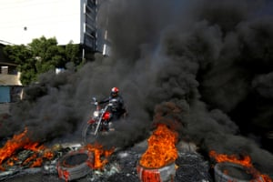 Najaf, Iraq. A man rides a motorcycle between burning tyres during anti-government protests