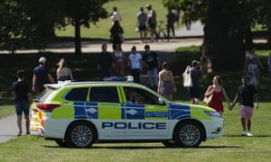 Police officers in a patrol car keep people moving in Greenwich Park, London