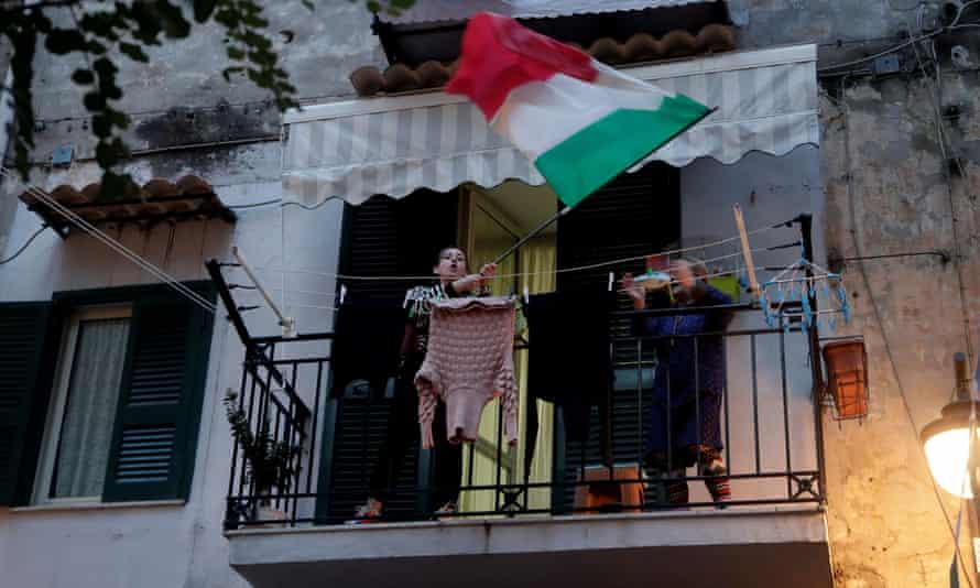 A woman waves an Italian's flag on a balcony in Naples