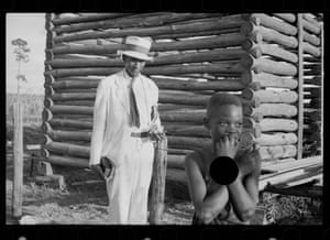 Man in white suit and boy with hands on his face, outside a wooden shack, with black circle on boy