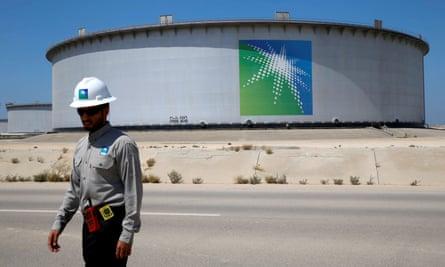 A Saudi Aramco employee walks near an oil tank at the Ras Tanura refinery and terminal in Saudi Arabia