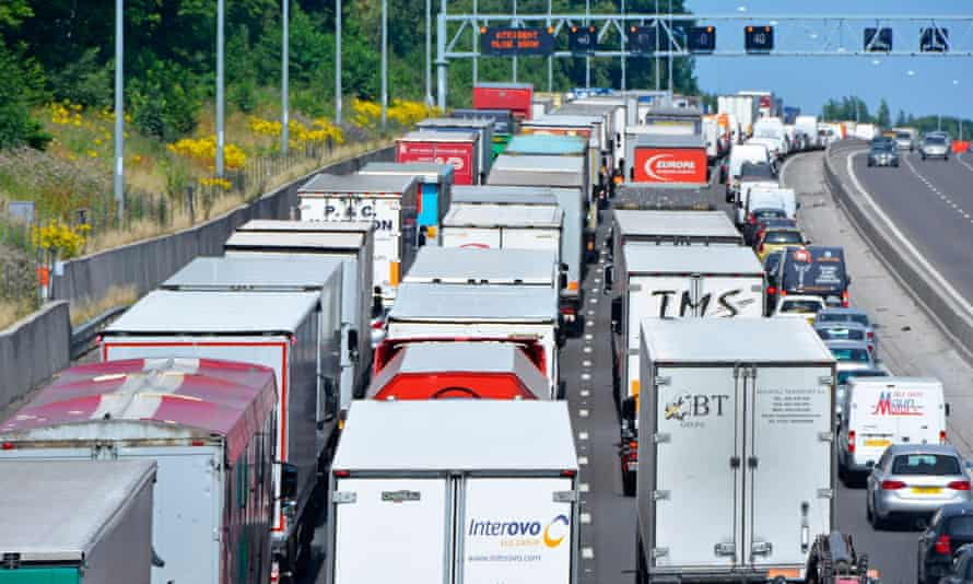 An accident on the M25 motorway, England, gridlocks lorries adding to pollution from vehicle fumes.