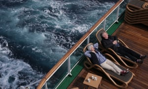 A couple relax on the rear deck of the Azura cruise ship on a Mediterranean holiday.