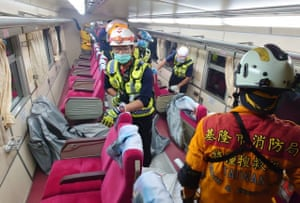 Search and Rescue team members remove bodies and from compartments on the train