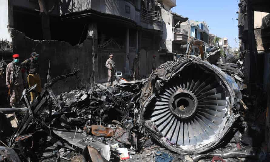 Security personnel stand beside the wreckage of a plane at the site after a Pakistan International Airlines aircraft crashed in a residential area in Karachi