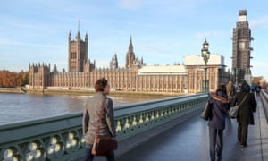 People walk across Westminster bridge next to the Houses of Parliament.