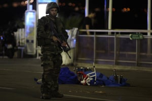A soldier stands next to a body covered with a blue sheet on the Promenade des Anglais