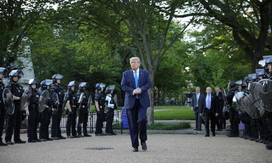 Donald Trump walks between lines of riot police on his way for a photo opportunity with a Bible outside St John's church in Washington on Monday.
