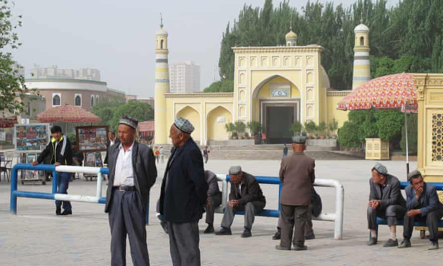 """On Liberation Avenue, outside Kashgar's Id Kah mosque, Uighur men watch security forces file past for the city's latest mass """"anti-terror"""" rally"""