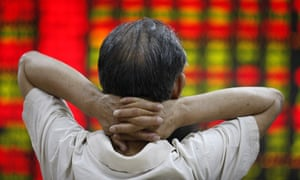 A man watches a screen board at a stock market