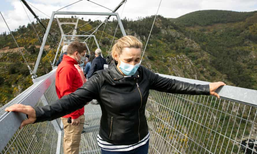 A visitor grips both sides of the bridge as she attempts to walk its 516 metre-span.