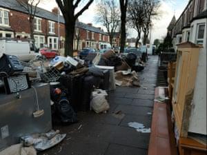 Destroyed belongings line the street on Warwick Road in Carlisle, 11 December