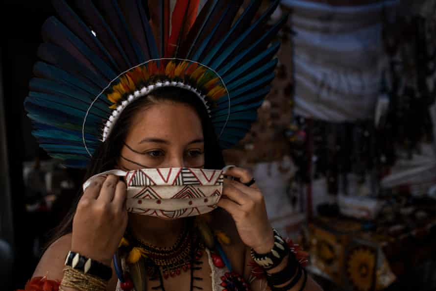 Samela Satere-Mawe, 23, shows a protective mask made by her women's association in Manaus, Brazil