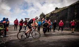 Alberto Contador either smiles or grimaces for the cameras as he ascends Alto de L'Angliru towards the end of Stage 20, a 117.5 km journey from Corvera de Asturias