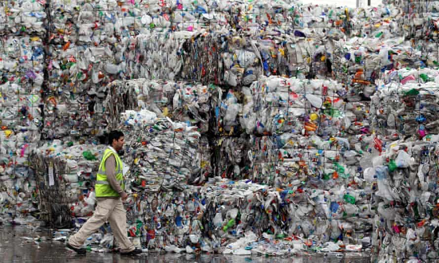 A man walks past stacks of plastic bottles at a recycling plant in Dagenham, east London