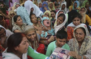A woman mourns near the body of her husband, Krishan Lal, an Indian army soldier who was killed in the village of Ghagriyal on the Pakistan side of the border of Kashmir.