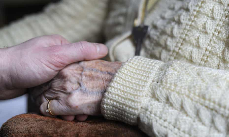 A young person clutching the hand of an elderly person