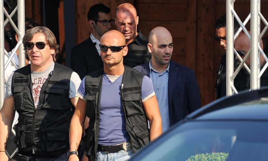 Roberto Saviano and bodyguards attend the 2013 Giffoni film festival in Italy.