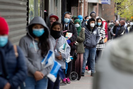 People wearing face masks wait in line to receive free food from a pantry in Brooklyn, New York, on 8 May.