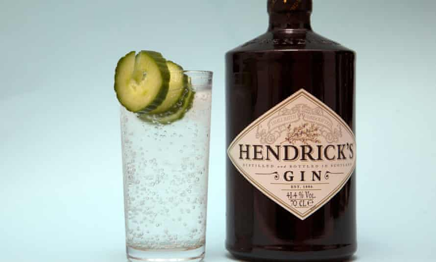 A bottle of Hendrick's gin and next to it a glass of gin and tonic.
