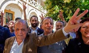 Şener Levent, Ali Osman Tabak and supporters make V for victory gestures outside court
