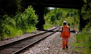 Network Rail worker walks beside tracks