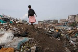 A schoolgirl walks back home amid the rubbish dumps of Mathare, Nairobi. 2010